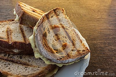 Toasted cheese sandwiches on the grill, situated on a white plate.