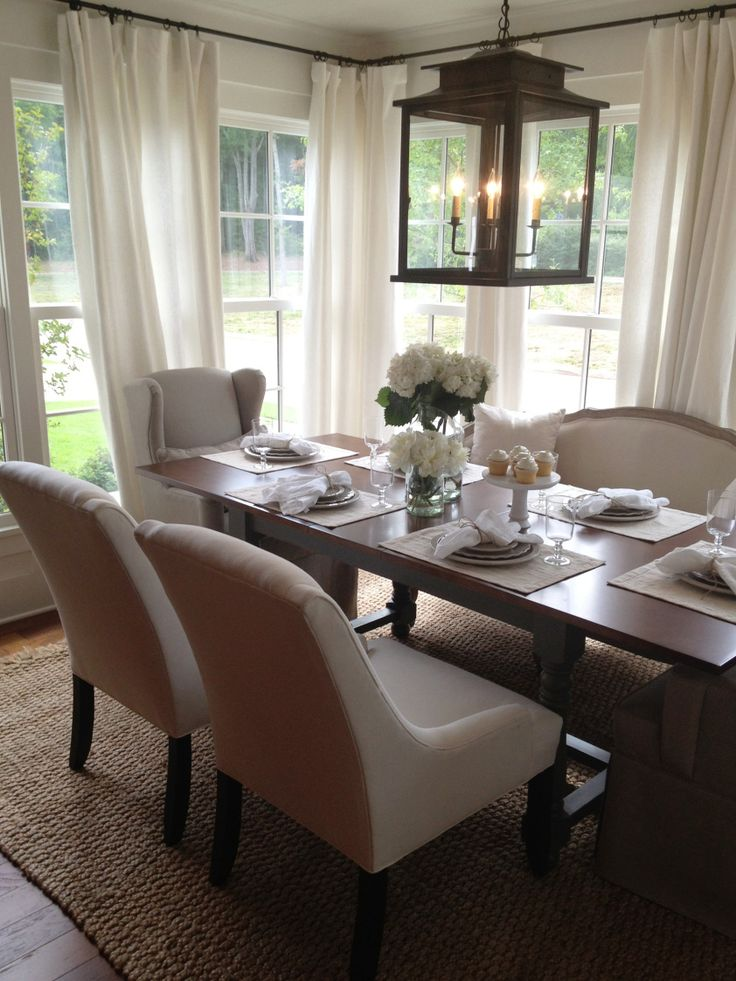 Pretty dining room with an oversized lantern, drapes & wood table