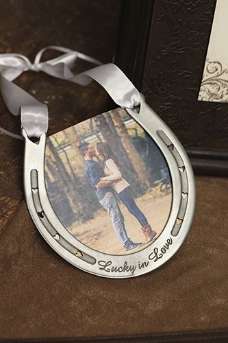 Lucky in Love Horseshoe - Genuine pewter horseshoe engraved with Lucky in Love hangs from white satin handle with satin streamers for tying rings. Add your own favorite photo for personal touch. See more wedding accessories  invitations at https://www.PrintedCreations.carlsoncraft.com.