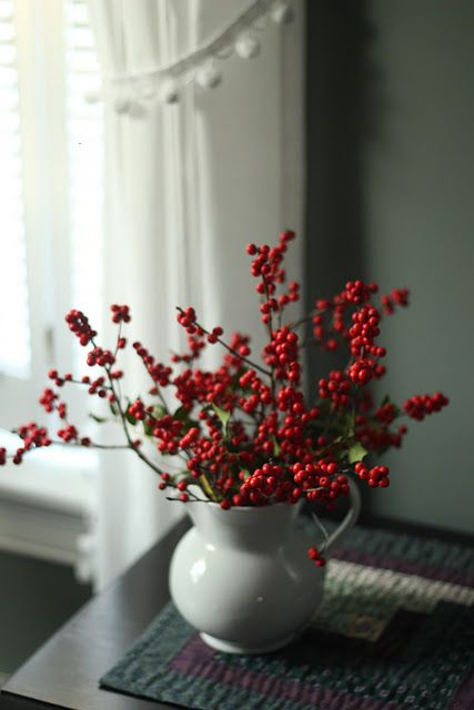 red berries in white pitchers.. very pretty but simple
