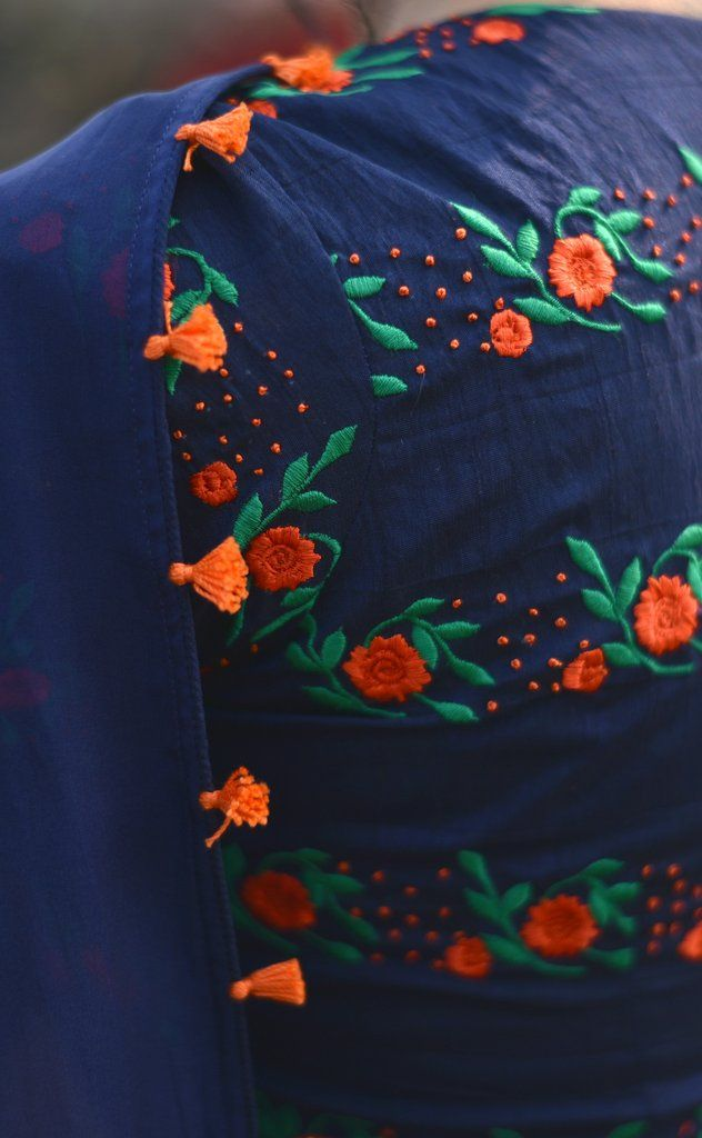PRODUCT DESCRIPTION: Featuring the Blue Flame saree in deep navy blue, 100% flat, pure silk chiffon fabric with neon orange tassels decorated along the edges. The synthetic raw silk blouse has neat, fresh orange flowerbeds embroidered with green foliage that stand out against the stark navy blue backdrop for beautiful results, as though emulating the bright sparks from a blue flame. NOTES:  This saree comes with an unstitched matching blouse piece, inner lining material and an unstitched…