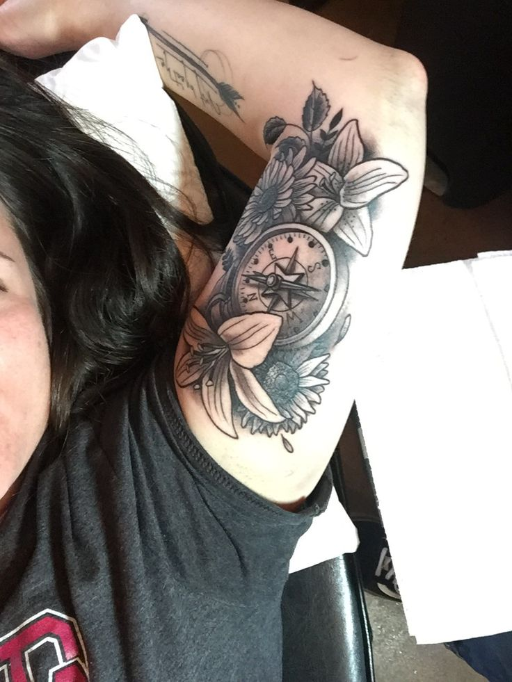 Girls with tattoos. Inner arm piece. Compass with lilies and sunflowers.