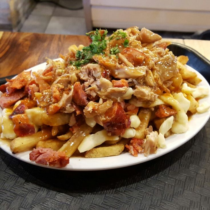 Traditional Canadian food with a Portuguese twist - Poutine with Portuguese grilled chicken and chorizo in Montreal, Canada