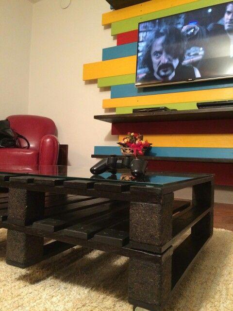 Struttura in legno colorata con mensole che sostiene la TV e tavolino in pallet
