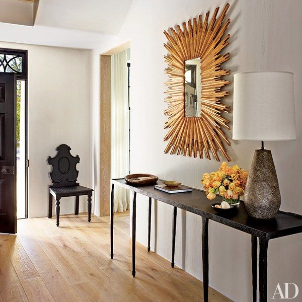 A starburst mirror from Lillian August animates the entrance hall; the console is by Crate and Barrel, and the chair is from English Country Antiques | archdigest.com