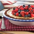Cherry Berry Cheesecake Pie - Luscious summertime fruits gloriously crown this easy cheesecake pie. Celebrate the red, white and blue with this vibrant fresh mixed berry cheesecake pie. Perfect for a picnic or 4th of July party, the smooth and creamy cheesecake pie filling in gingersnap crust will be a crowd pleaser.