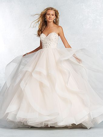 A beautiful wedding dress with a strapless, sweetheart bodice, natural waist, hi-low overlay ball gown skirt, and chapel train.