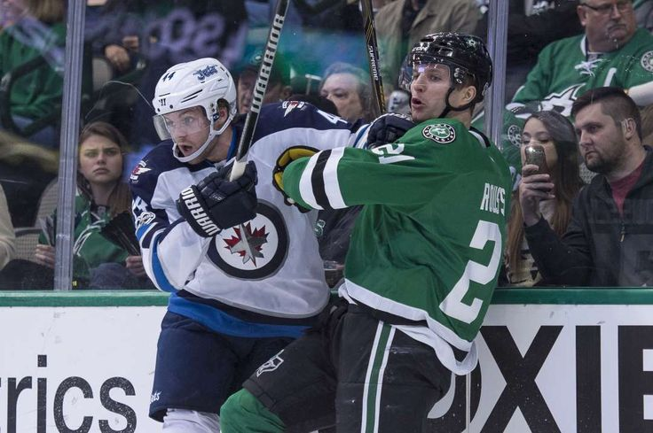 Into the boards:   Winnipeg Jets defenseman Josh Morrissey checks Dallas Stars left wing Antoine Roussel during the first period at the American Airlines Center in Dallas on Feb. 2.
