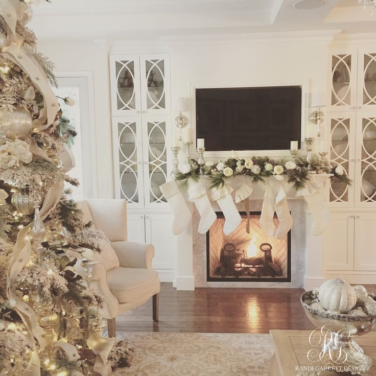 Elegant white Christmas tree by Randi Garrett Design. Neutral mantel with beautiful built ins.