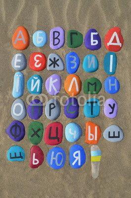 Ukrainian alphabet on colourful stones over the sand