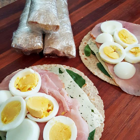 Makes these simple Grab & Go Breakfast Wraps once and have ready for the work week! Sliced hard-boiled egg, ham, cheese, and spinach wrapped in a tortilla.