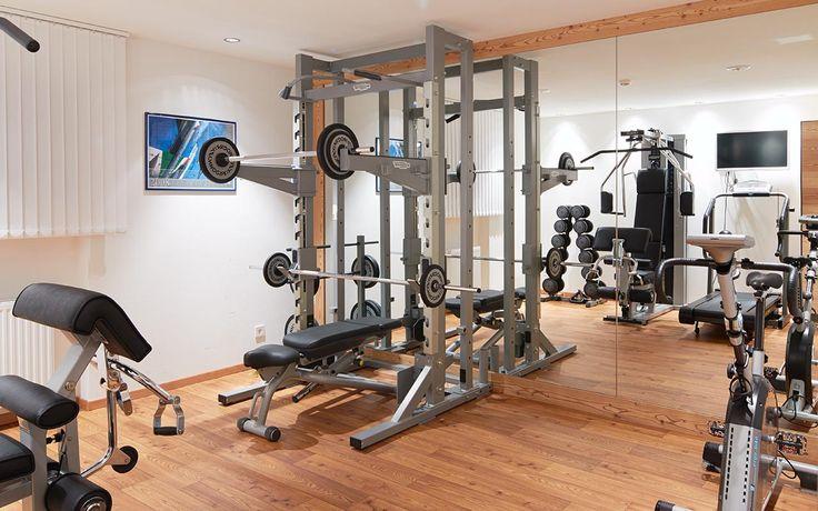 Sala fitness dello Chalet Gerard con strumenti, pareti bianche e pavimento in legno