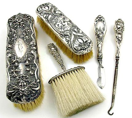 Lovely grouping of five Unger Brothers sterling silver hollow-ware vanity dressing table pieces; large and small hair brush, clothing lint brush, button hook, and ink eraser.