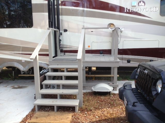 Steps, rails and a small landing upgrade the entry to a cute RV porch (Piney Ridge RV)