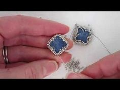 Leslie shows you how to create a beaded bezel for a 14x14mm square kyanite bead, and then how to finish it into a quatrefoil shape. Knowledge of peyote stitc...
