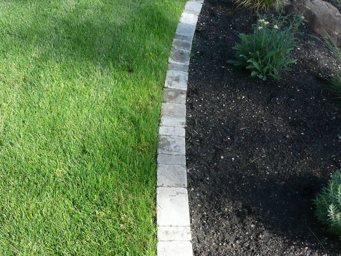 Border for garden in front of rock wall. Landscaping
