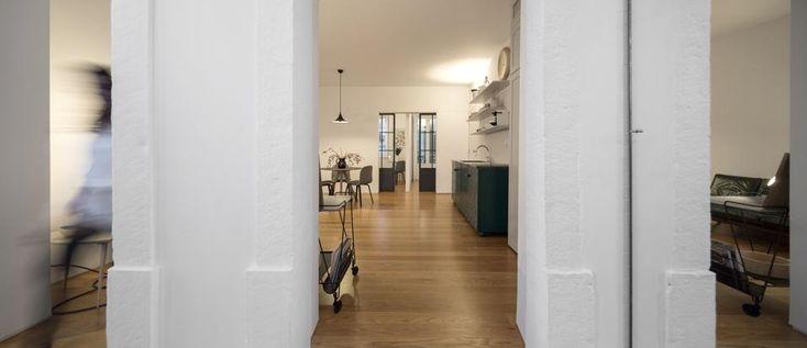 60mq di idee. Lo spazio centrale riflette la luce esterna sul bianco delle pareti, il parquet dà calore agli ambienti. Sul fondo le camere private risultano connesse e nascoste dietro le due porte disposte in maniera simmetrica.