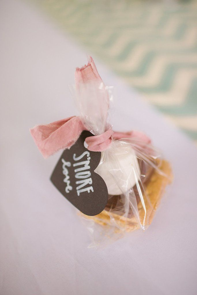 """This might be a good treat for receptions held at night. Guests will get to bring home a quintessential late-night snack, and writing a sweet note like """"S'more love"""" adds the perfect tie-in to your wedding."""