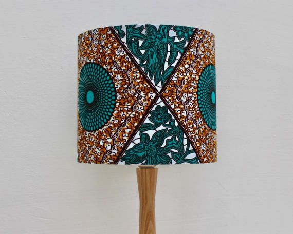 Elegant, African wax block print fabric circular drum lampshade. Handmade in the UK using striking print.  The handmade lampshade can be used for the ceiling or a table lamp. Get in touch if you would like the lampshade supplied with a wooden ash stand at an additional cost of £25.00.  Please see the Tropikala store for other fabric designs available.  Product information: - Dimensions: diameter 20 cms, height 18 cms - Fabric backed with a fire resistant PVC - Recommended to be used with a…