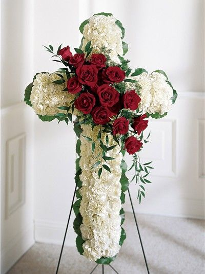 A funeral flower cross of white carnations with a red rose spray