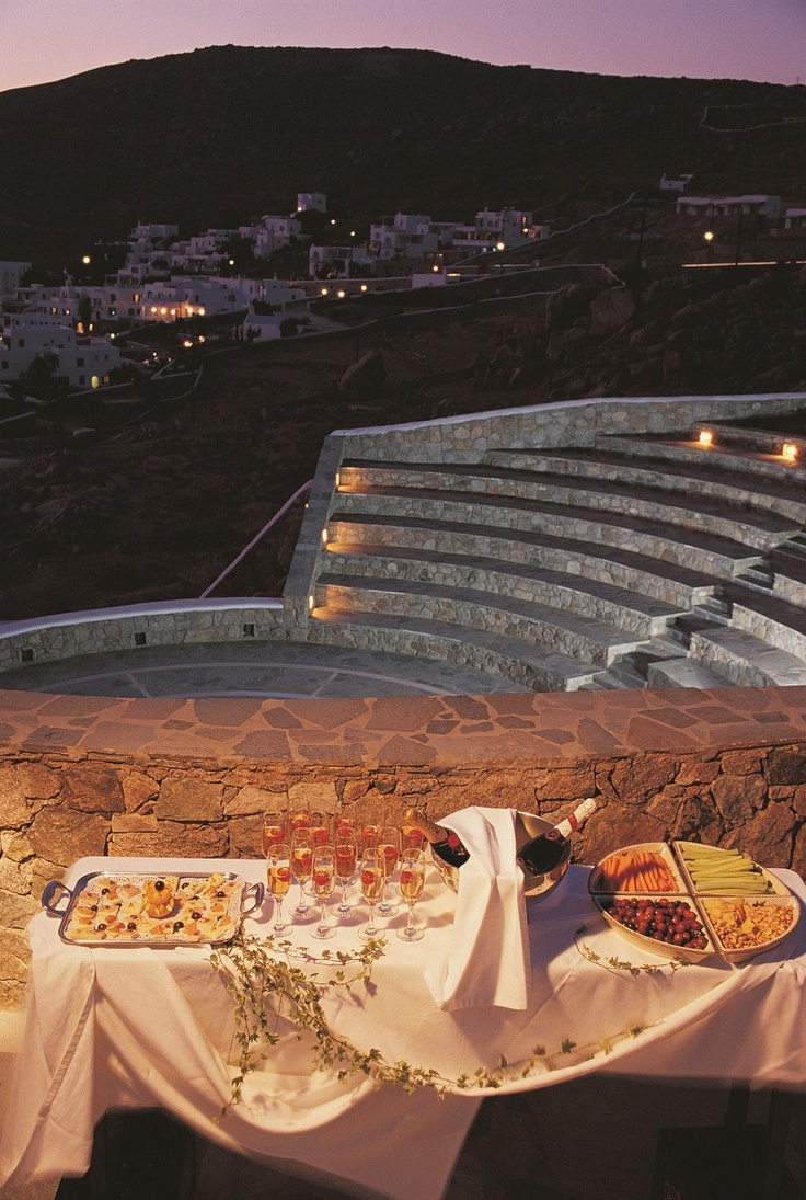 Cocktail setup at Stone-built outdoor Amphitheater at Mykonos Grand Hotel & Resort. Champagne ready to be served.
