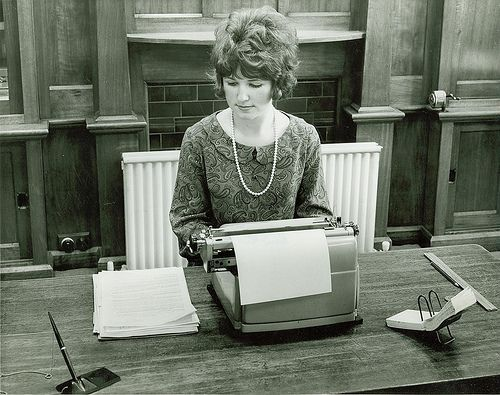 Secretary typing in front of her new gas heating system 1964. Vintage 1960s office. #tafe #education #geelong #learning