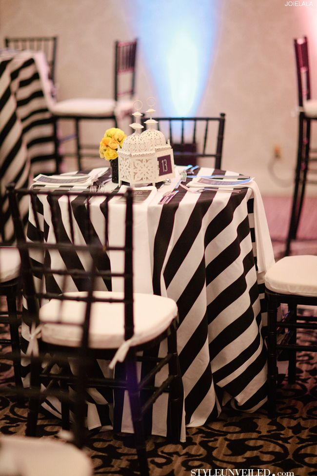 A Black and White Striped Table Linen topped with Yellow Flower details and  Black vases and