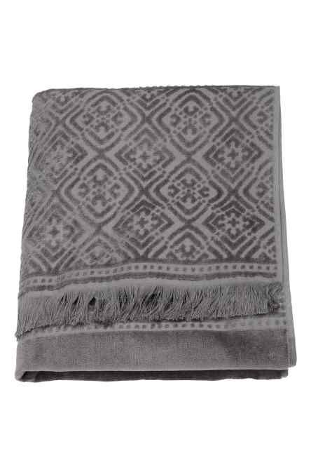 Osuška z bavlněného froté s žakárově tkaným vzorem. Na jedné z kratších stran má poutko a na koncích třásně.