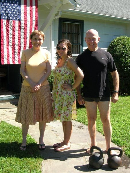 """""""My grandfather is the star of many awkward family photos. Here, he poses pantsless, with a pair of kettlebells, artistically composed at his feet to highlight his lack of pants and booty short spandex. The flag in the background pretty much says it all: this is AMERICA."""" (submitted by Hannah)"""