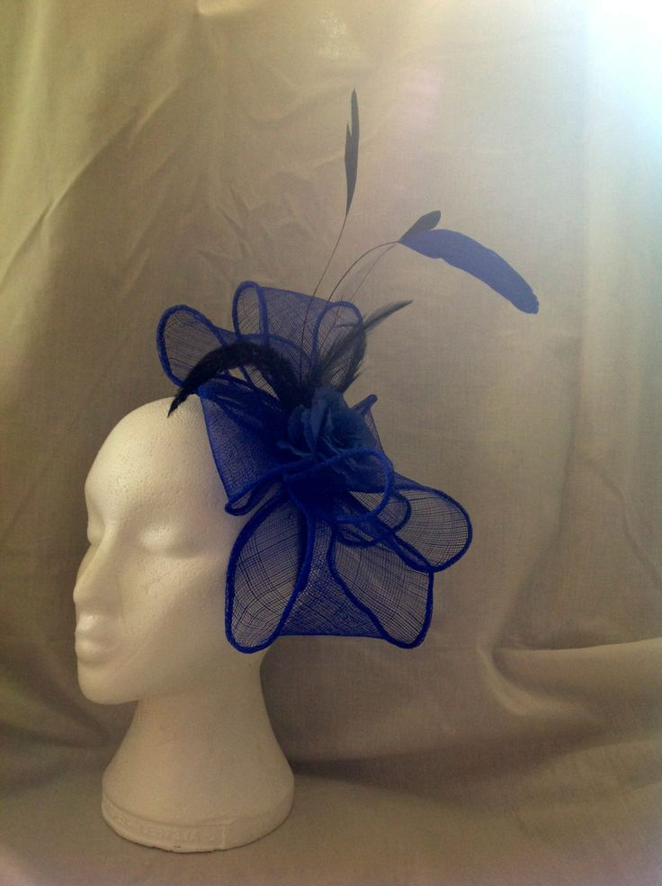 The Penny is a large fascinator on a black head band the centre piece is a large sapphire blue flower with diamante detailing surrounded by large loops of sapphire blue sinamay with matching feathers to finish. $95 AUD.