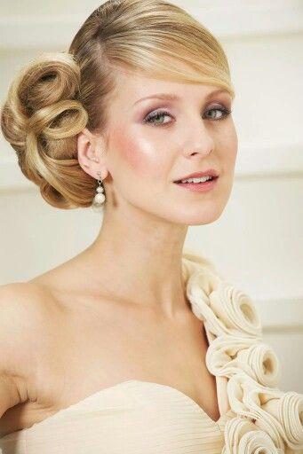 Asymmetrisch bruidskapsel, dikke knot schuin in de nek met een lage, schuine lok. Hairstyling: Jolande Goverde