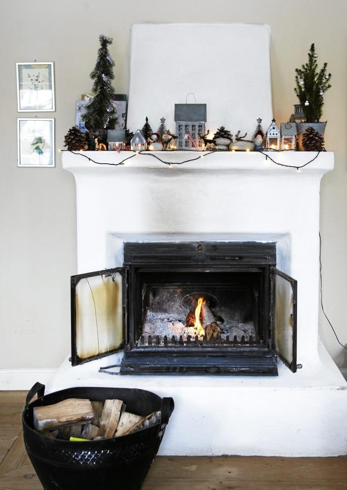 Ingenting skaper stemning som levende lys og fyr i peisen. På peishyllen har små juletrær og telys fått sin plass.