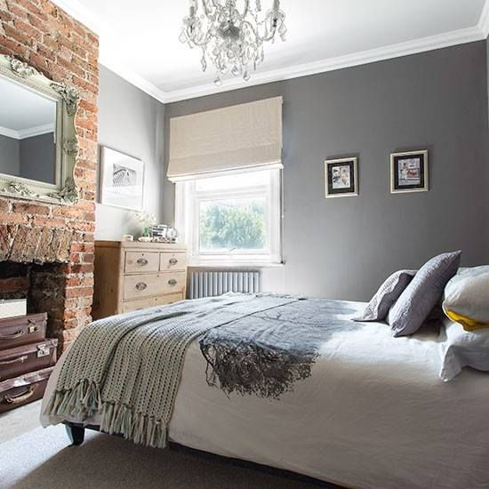 Beautiful grey and white bedroom, and feature red brick fireplace.