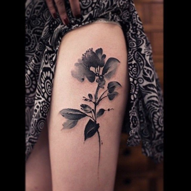 Black and white watercolor flower thigh tattoo