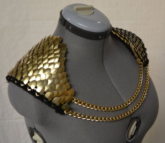 Epaulets or angel wings, these scalemail armor pieces are eye catching and dramatic with shiny gold scales on black yarn. Gold chains front and