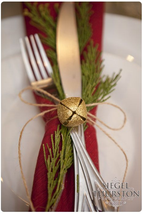 Table setting with red napkin and green garland tied up with twine and a gold bell