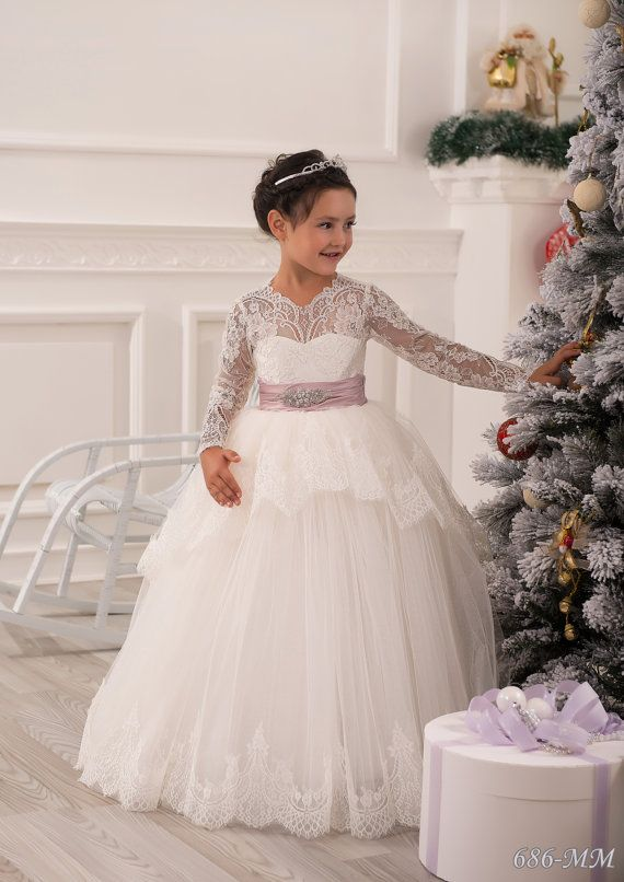 Gorgeous ivory flower girl dress with multilayered skirt, lace corset with long lace sleeves, buttons, zipper and satin stripe with bow.  Item
