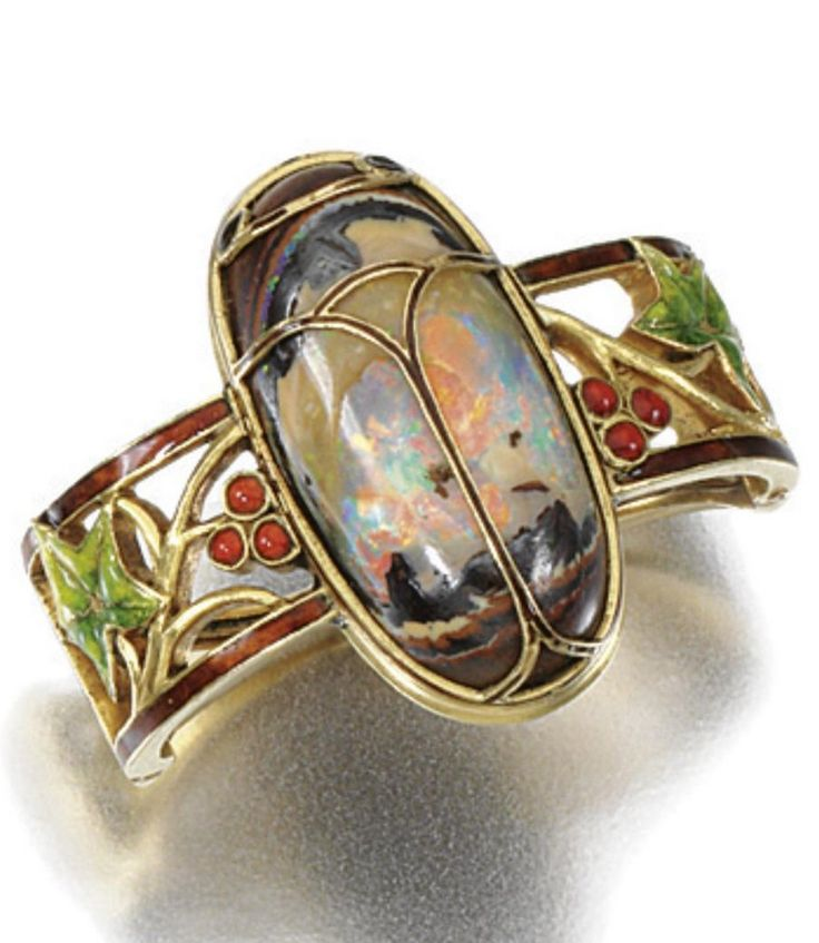 AN ART NOUVEAU GOLD ENAMEL AND OPAL SCARF CLIP, FOUQUET, 1900s. Centring on an opal cicada set between open work enamel ivy leaves, indistinctly signed Fouquet.