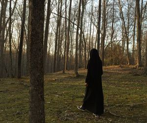 Niqabi walking through the woods