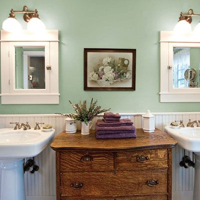 An antique oak dresser sits between two pedestal sinks, providing storage for
