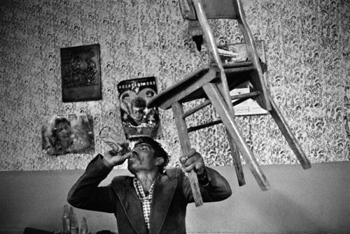 Greece, Alexandroupolis. In a coffee shop named the tavern of Ali. A Muslim gipsy holds up a chair without losing balance to prove his sobriety. 1991,  by Nikos Economopoulos