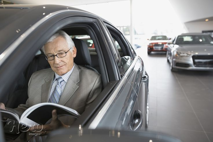 Photograph Man with brochure inside car in dealership showroom by Hero Images  on 500px