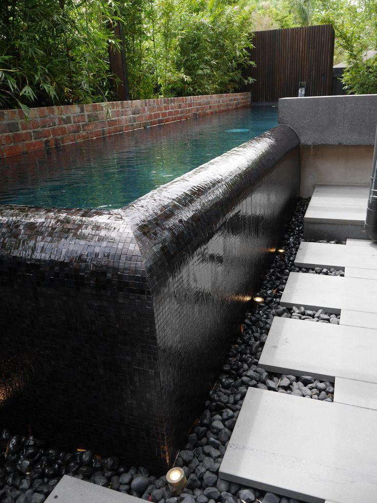 Corner detail of this fantastic infinity edge pool with a black glass mosaic tile interior