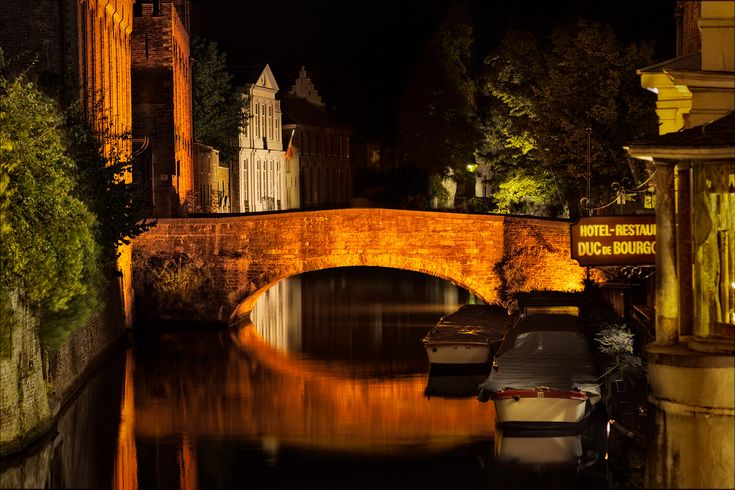 A quiet night on the canal, lit by neon light in Bruges, Belgium.