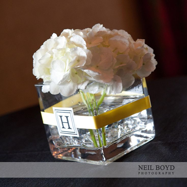 White hydrangea wedding reception centerpieces with letter monogram and yellow ribbon.