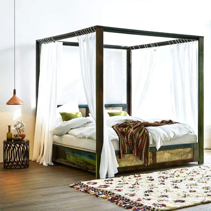 Himmelbett im Ethno-Stil: Dunkelbraunes Bettgestell, weiße Vorhänge, Kissen und Decken und ein Teppich vor dem Bett
