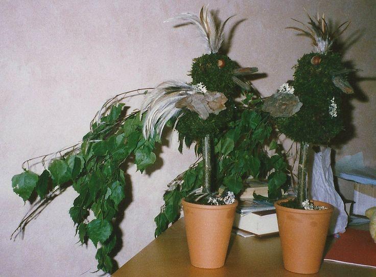 stok in een bloempot vastgezet(bv met cement of gips. Daarop grijze grote schuimbol met kleine erop. bedekken met mos, als snavel boomschors, als staart berkentakken. afmaken met veren etc.