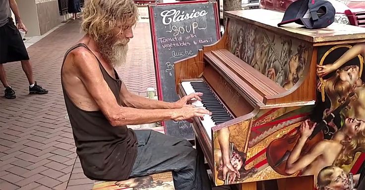 A homeless man down on his luck performs for impressed onlookers.