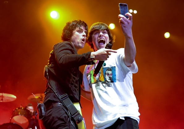 Green Day's Billie Joe Armstrong takes a photo with a fan onstage at a show at Toronto's Air Canada Centre.