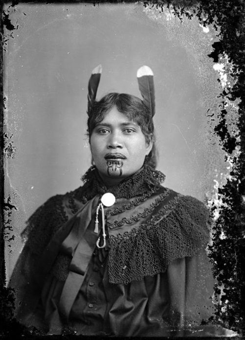 Unidentified Maori woman with a chin moko, feathers in her hair, and European clothing, [ca 1895]  Unidentified  Maori woman, circa 1885, with a chin moko and feathers in her hair. She  wears European style clothing. Location and photographer unknown.